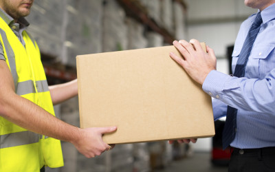 Warehouse worker and manager help each other move a cardboard box.