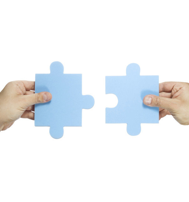 Two hands connecting puzzle pieces