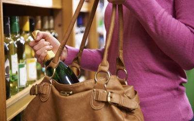 Woman Stealing Bottle Of Wine From Supermarket