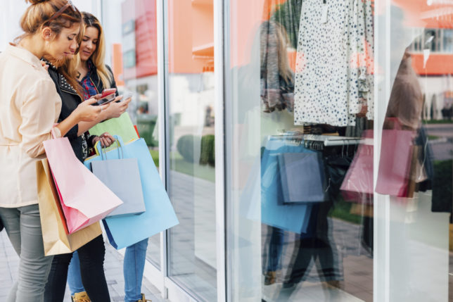 Teens looking at mobile phone model of clothes in front of shopping windows