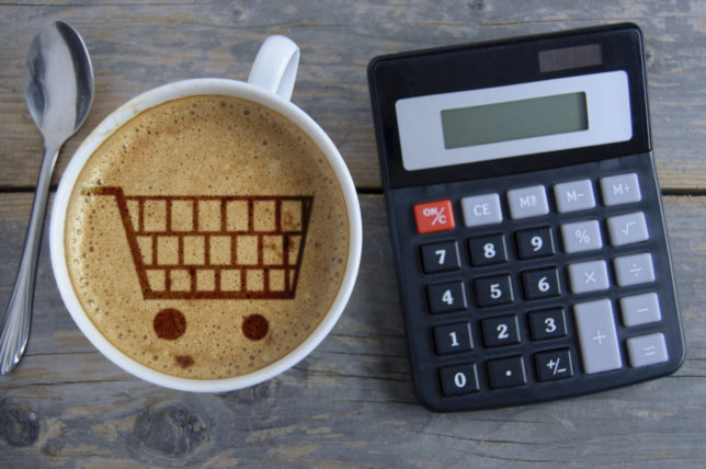 Shopping cart symbol inside a coffee cup by a calculator