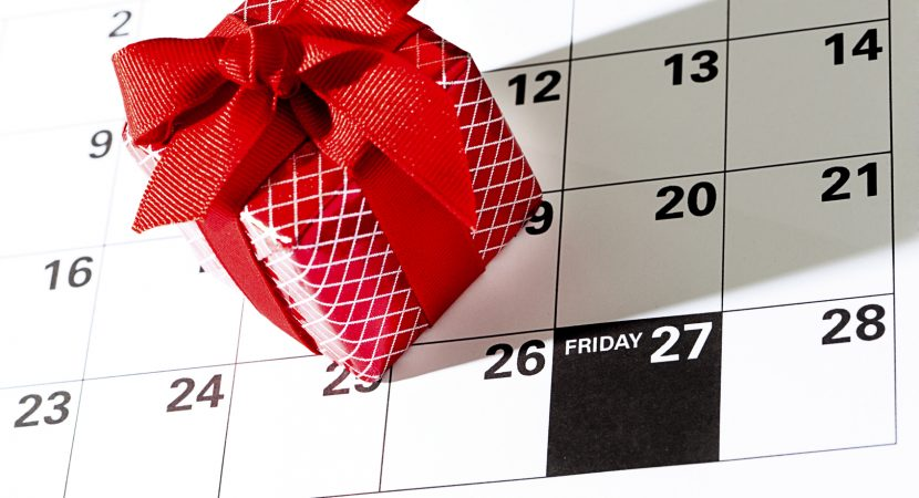 Black Friday Sale date marked on a calendar with a Christmas gift in bow and ribbon. November 27 Friday, 2015. The traditional Friday after Thanksgiving date is the kick off date for retailers for Christmas retail, the biggest Christmas shopping date of the holiday season. Close-up photography in vertical format of a calendar page.