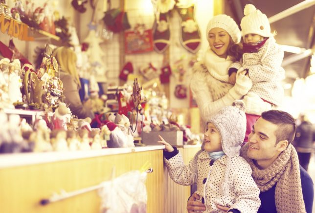 Happy family choosing Christmas decoration at Christmas market. Focus on girl and man